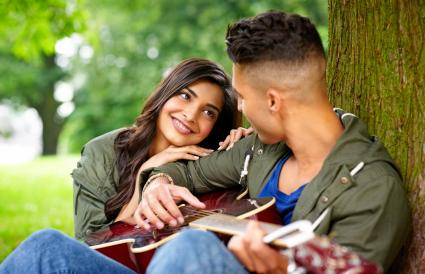 Romantic couple with guitar outdoors