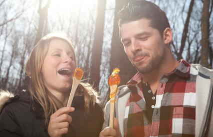 couple eat Maple taffy on a sunny day