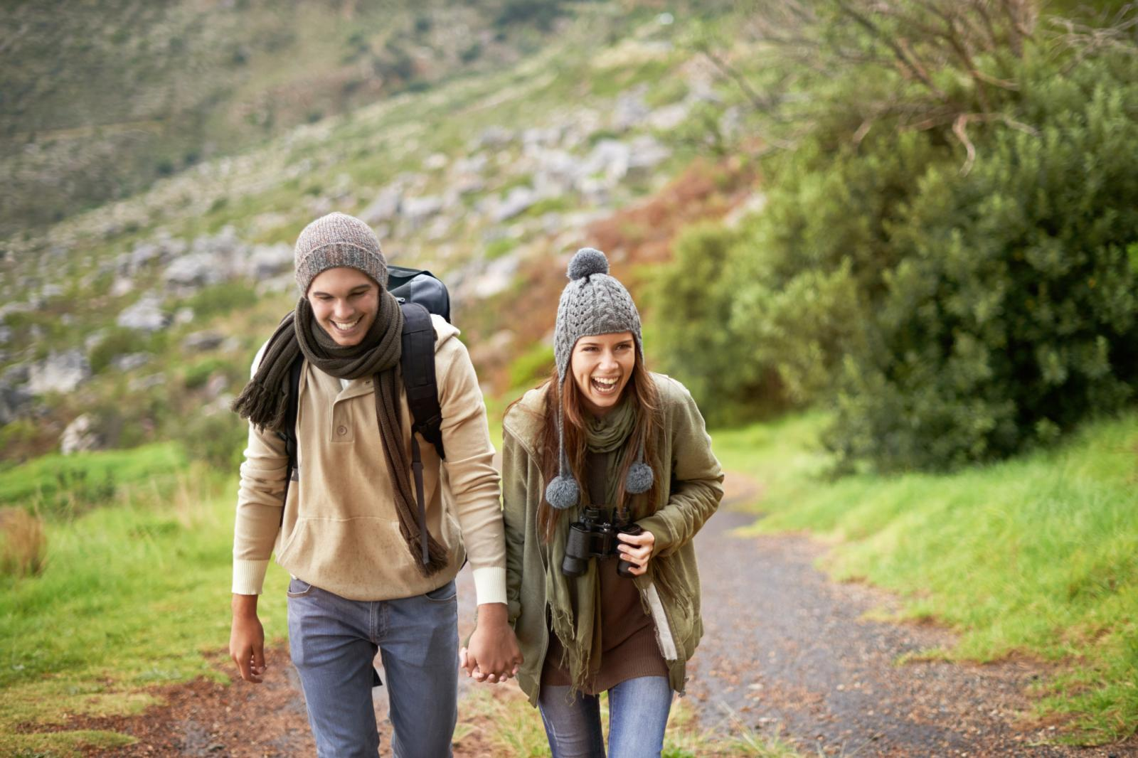 Young couple wrapped up warmly and hiking on a mountain trail together
