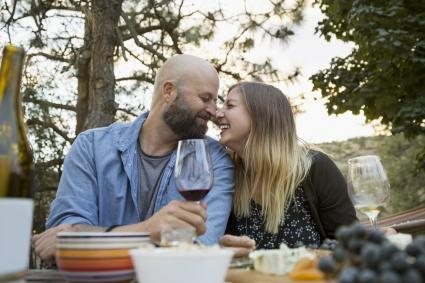 Affectionate couple rubbing noses and drinking wine at patio table
