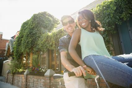 Playful couple riding bicycle on sunny sidewalk