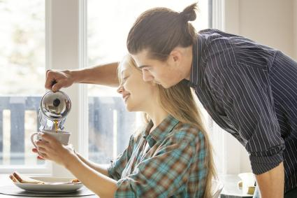 Man pouring coffee in cup for girlfriend at home