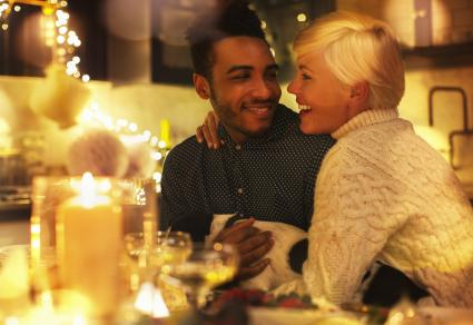Affectionate couple with dog at candlelight Christmas table