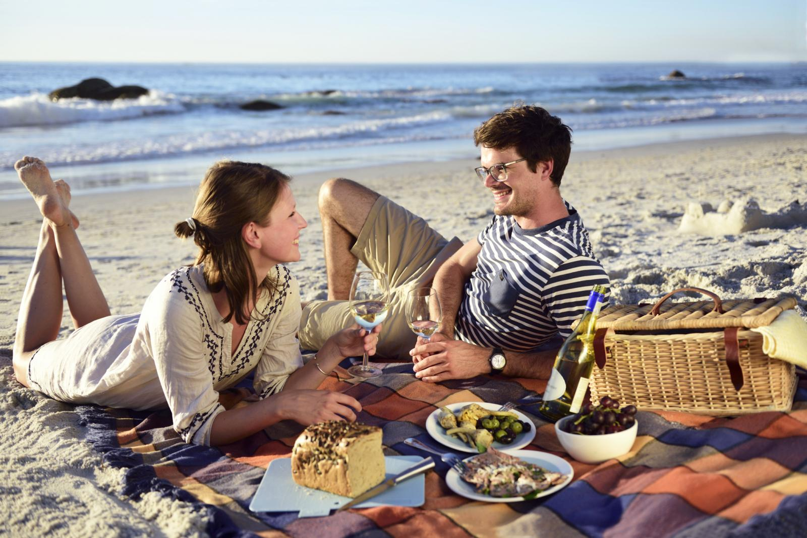 Happy couple having a picnic on the beach