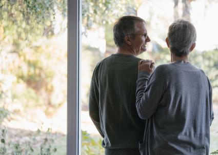 Senior couple standing at window
