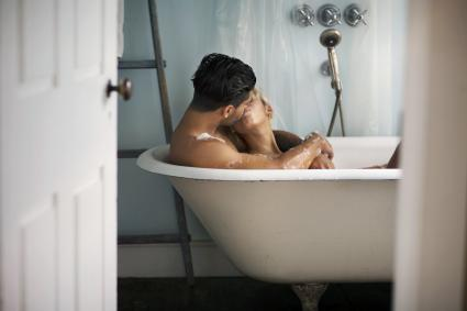 Young couple kissing in bathtub at home