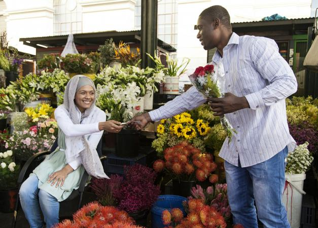 Many buying flowers from a flower market stand