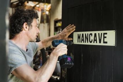 Man fixing mancave sign on wooden door