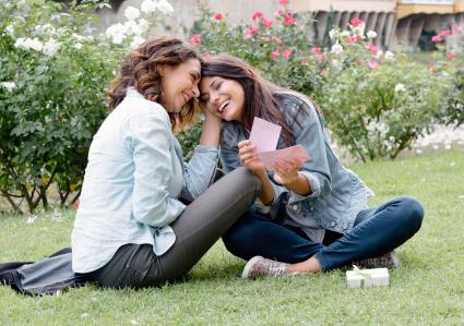 Lesbian couple sitting on grass exchanging love letter