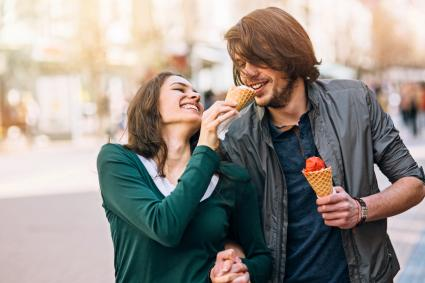 Young couple sharing ice cream and laughing