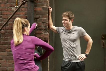 Young male and female runners warming up in alleyway while flirting