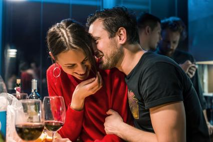 Couple drinking wine at party in apartment