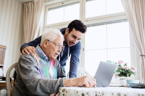 Man volunteer helping senior with computer