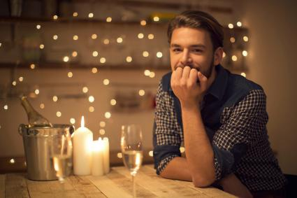Man on a date with lit candles, string lights and champagne