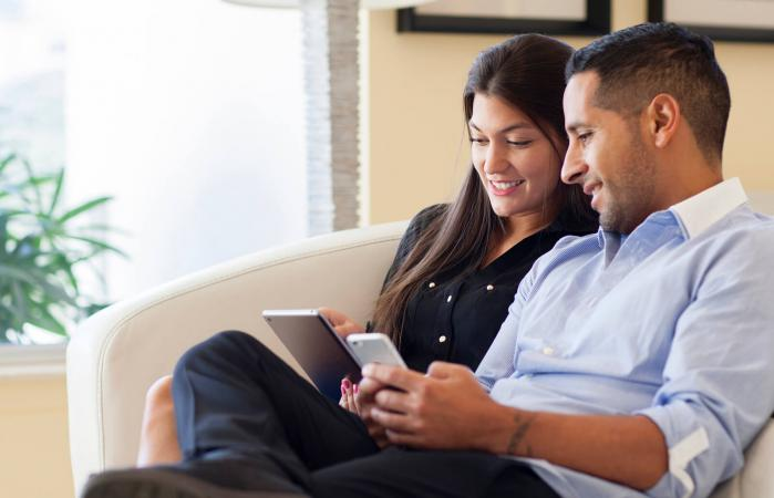 couple using digital tablet in armchair