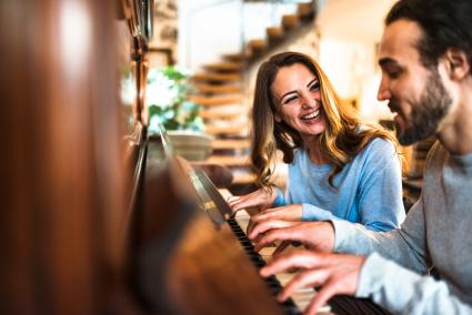 Woman and man playing piano together