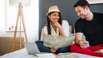 Young couple with laptop and map at home, planning a journey