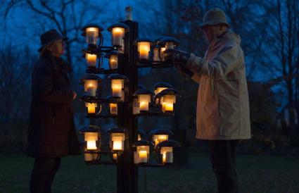 Two adults lighting candles at the cemetery