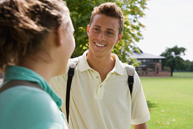 Teen girl and boy flirting outside school