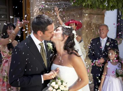 Guests throwing confetti over kissing bride and groom,