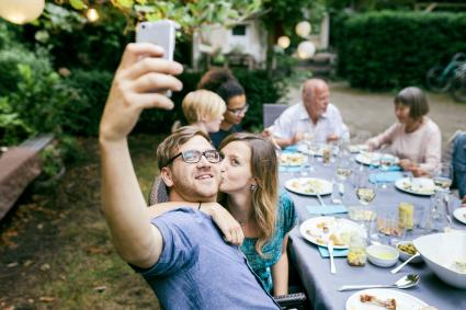 Couple Taking Selfie During BBQ With Family