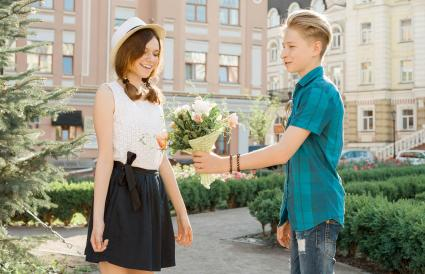Teen boy giving girlfriend flowers