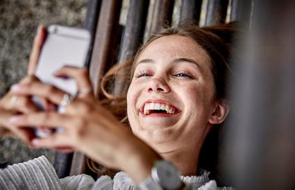 woman lying on a bench using cell phone