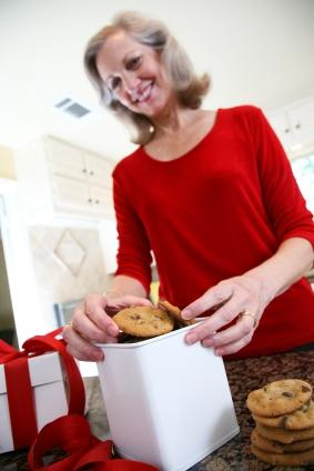 Woman packing homemade cookies into a gift tin
