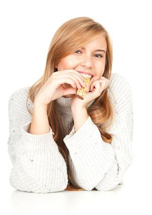 woman eating cereal bar