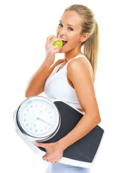 Woman holding scale and eating apple