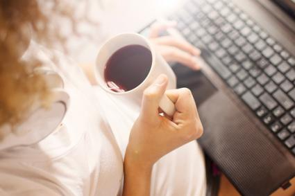Girl typing on laptop with cup of coffee