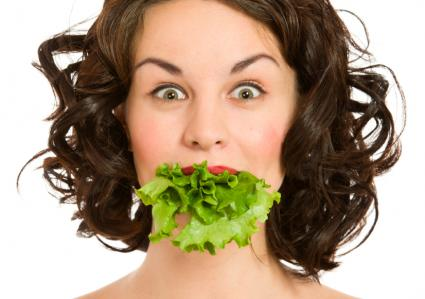 Woman with lettuce in mouth