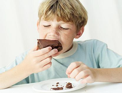 Boy eating chocolate brownie