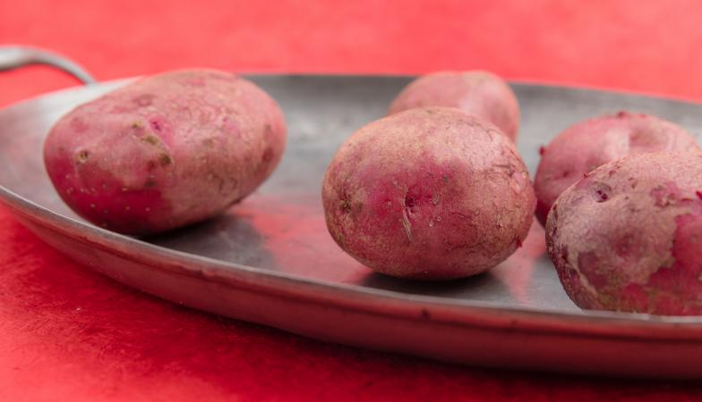 Washed red potatoes on a pewter plate