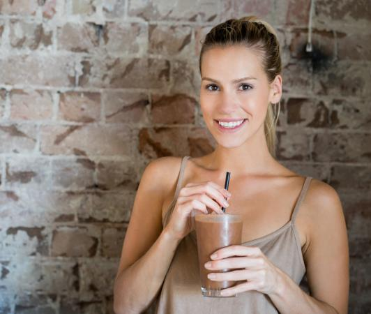 Smiling caucasian woman with chocolate shake