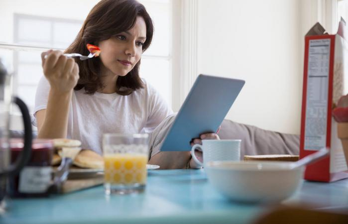 Woman using digital tablet at breakfast table