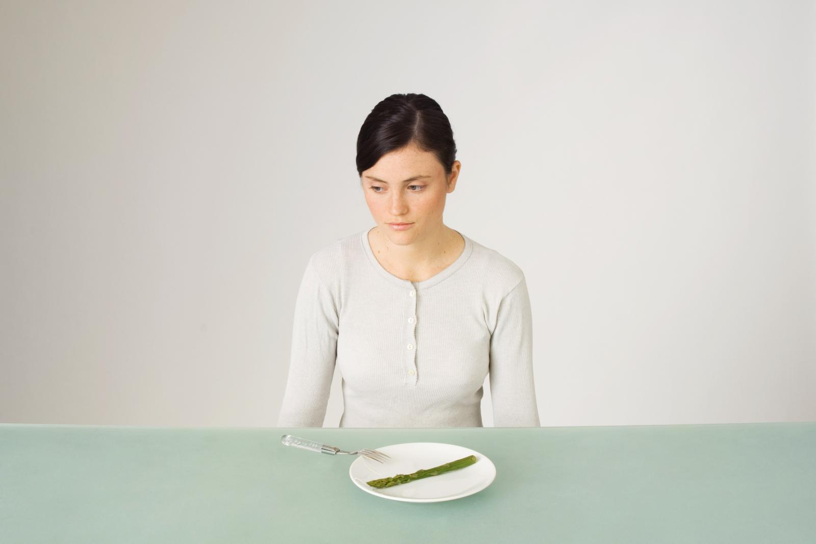 Young woman sitting in front of plate with single asparagus