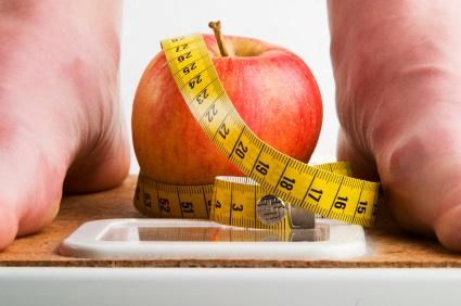 Person on scale with apple and tape measure