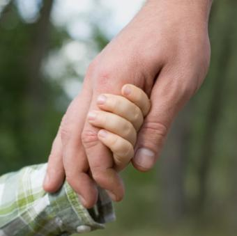 Father holding little boy's hand