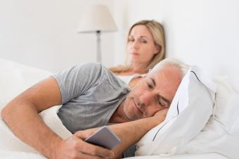 shady texting by man in bed