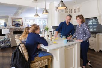 Parents and teens talking in kitchen