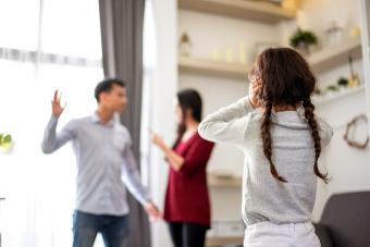 Daughter looking at parents fighting in house