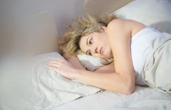 Sad woman lying in bed