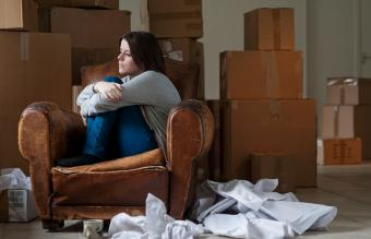 Sad woman in armchair in new home