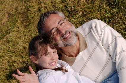 Grandfather and grandchild on grass