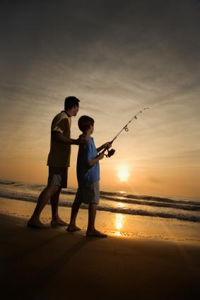 Man and boy fishing in surf at sunset