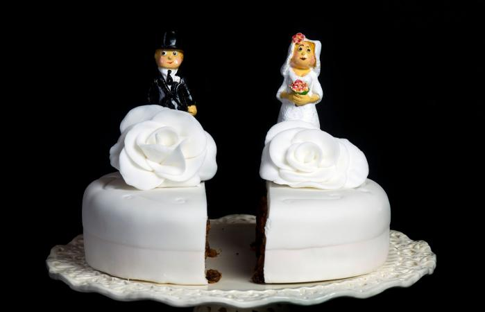Wedding cake cut in two symbolizing divorce