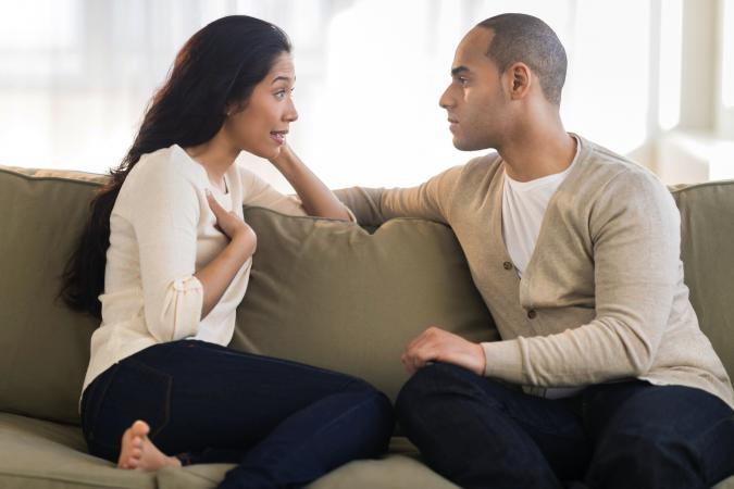 Young couple sitting on couch and having a conversation