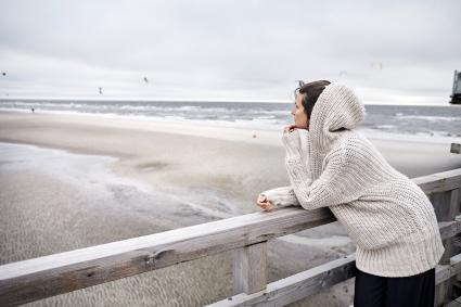 Woman standing on footbridge by the sea
