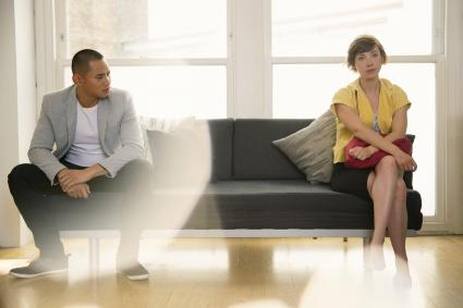 Couple sitting apart in a couch
